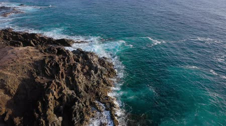montanhas rochosas : View from the height of a deserted coast. Rocky shore of the island of Tenerife. Aerial drone footage of sea waves reaching shore