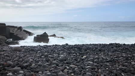 pedras : Timelapse of a large pebble beach and ocean waves reaching shore. Rocky shore of the island of Tenerife