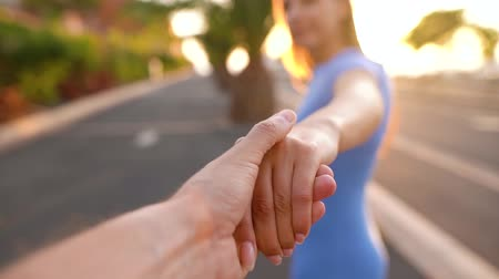 executar : Follow me - woman extends her hand to the man, he takes her hands and gently strokes