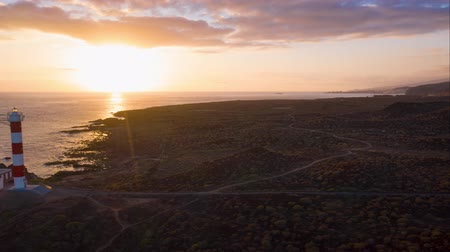 nuvens : View from the height of the lighthouse silhouette Faro de Rasca at sunset on Tenerife, Canary Islands, Spain. Wild Coast of the Atlantic Ocean. Hyperlapse Vídeos
