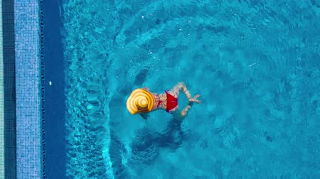 cappello rosso : View from the top as a woman in a red swimsuit and a big yellow hat swims in the pool