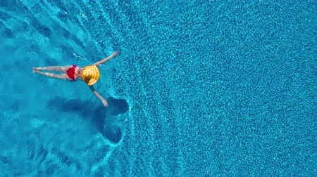 nurkowanie : View from the top as a woman in a red swimsuit and a big yellow hat swims in the pool