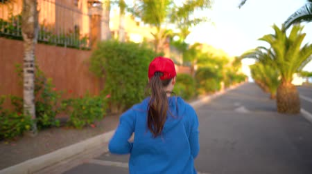 závodní dráha : Woman runs down the street among the palm trees at sunset, back view. Healthy active lifestyle