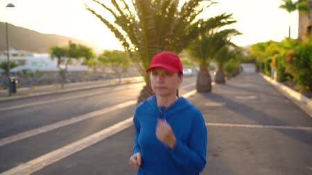 závodní dráha : Woman runs down the street among the palm trees at sunset. Healthy active lifestyle