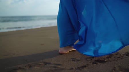 luxus : Legs of a woman in beautiful blue dress walking along a black volcanic beach