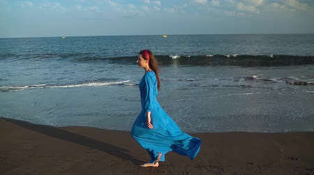 luxus : Woman in beautiful blue dress walking along a black volcanic beach