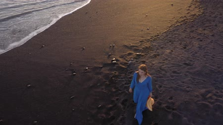 kanári : Aerial view of a girl in a blue dress walking on the beach with black sand. Tenerife, Canary Islands, Spain Stock mozgókép