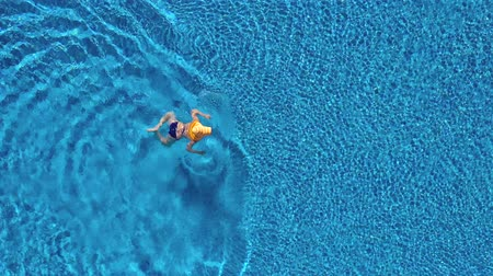 plavat : View from the top as a woman in a blue swimsuit and a big yellow hat swims in the pool