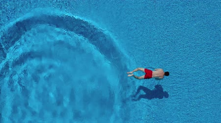 plavat : View from the top as a man dives into the pool and swims under the water Dostupné videozáznamy