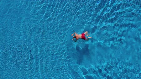 nurkowanie : Aerial view of man in red shorts swims in the pool