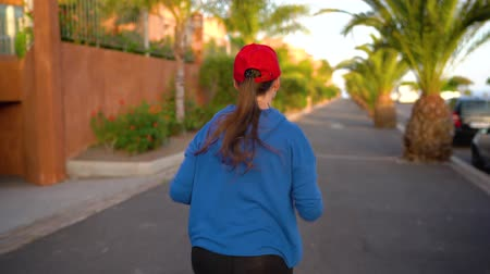 perspektif : Woman runs down the street among the palm trees at sunset, back view. Healthy active lifestyle