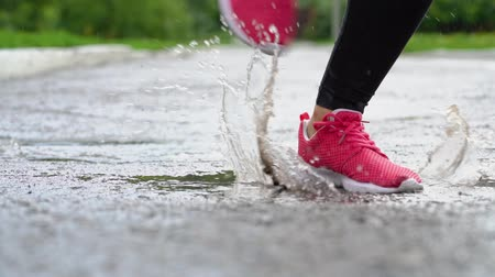 spat : Legs of a runner in sneakers. Sports woman jogging outdoors, stepping into muddy puddle. Single runner running in rain, making splash. Slow motion