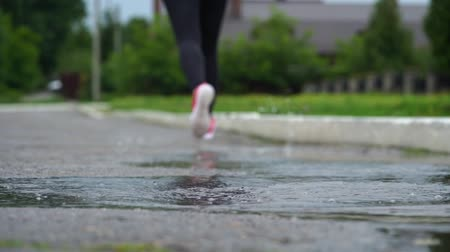 spat : Legs of a runner in sneakers. Sports woman jogging outdoors, stepping into muddy puddle. Single runner running in rain, making splash. Back view. Slow motion