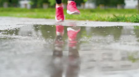 cipő : Legs of a runner in sneakers. Sports woman jogging outdoors, stepping into muddy puddle. Single runner running in rain, making splash