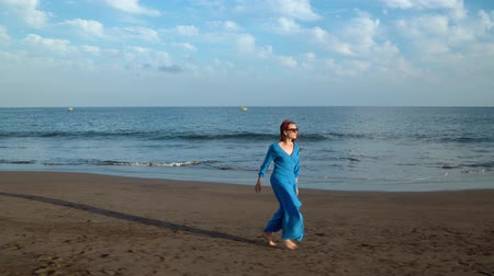 luxus : Woman in beautiful blue dress running along a black volcanic beach