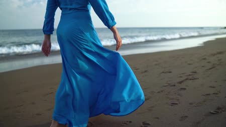 luxus : Woman in beautiful blue dress walking along a black volcanic beach. Slow motion
