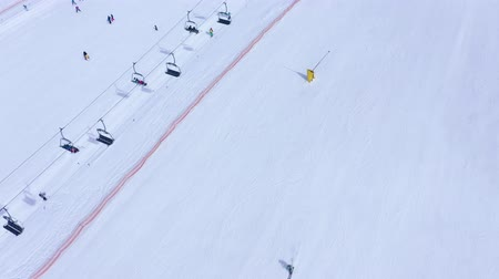 arrasto : Ski slope - ski lift, skiers and snowboarders going down. Aerial view