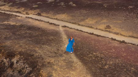 pedras : Aerial view of woman in a beautiful blue dress and hatwalking to the top of a mountain in a conservation area on the shores of the Atlantic Ocean. Tenerife, Canary Islands, Spain