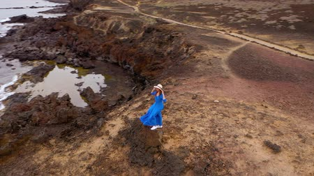 pedras : Aerial view of woman in a beautiful blue dress and hat stands on top of a mountain in a conservation area on the shores of the Atlantic Ocean. Tenerife, Canary Islands, Spain. Slow motion