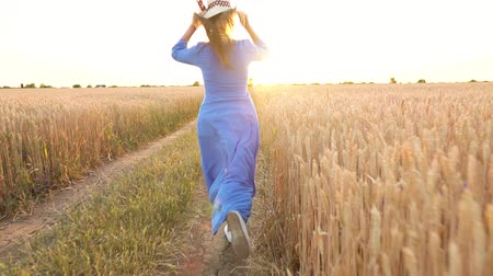 vychovávat : Beautiful woman in a blue dress and hat runs through a wheat field at sunset. Freedom concept. Wheat field in sunset. Shooted at different speeds: normal and slow motion