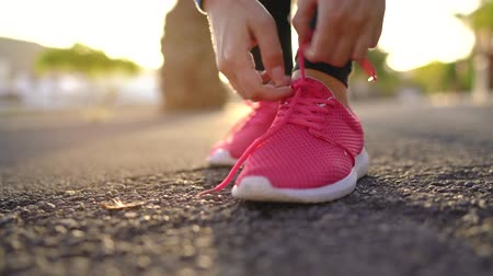 folha : Close up of woman tying shoe laces and running along the palm avenue at sunset