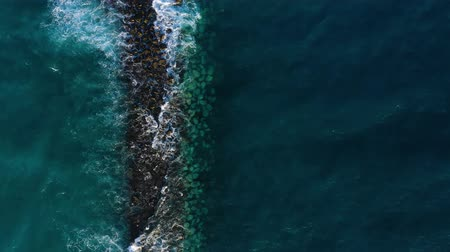 sopečný : Top view of the surface of the Atlantic Ocean near the coast - waves roll through the breakwater. Coast of the island of Tenerife