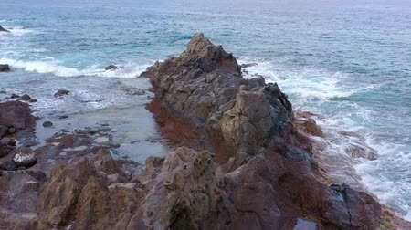 바위가 많은 : Rocky shore of the island of Tenerife. Aerial drone footage of sea waves reaching shore