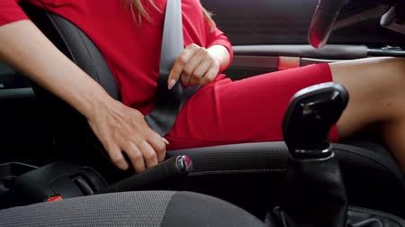 ubezpieczenia : Woman in red dress fastening car safety seat belt while sitting inside of vehicle before driving