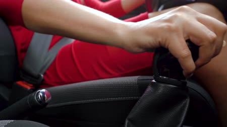přezka : Close-up of woman driver in a red dress fastens her seat belt, changes gear and starts moving Dostupné videozáznamy