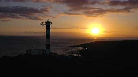 stone : View from the height of the lighthouse silhouette Faro de Rasca at sunset on Tenerife, Canary Islands, Spain. Wild Coast of the Atlantic Ocean Stock Footage