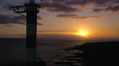 destinos de viagem : View from the height of the lighthouse silhouette Faro de Rasca at sunset on Tenerife, Canary Islands, Spain. Wild Coast of the Atlantic Ocean Stock Footage