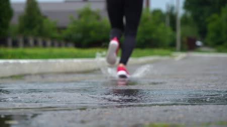 pocsolya : Legs of a runner in sneakers. Sports woman jogging outdoors, stepping into muddy puddle. Single runner running in rain, making splash. Back view. Slow motion