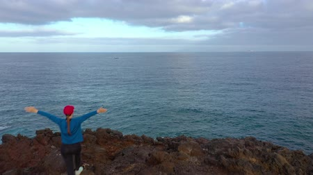 pedras : Flying over woman in sportswear after jogging stands on top of a rock and enjoys the scenery in a conservation area on the shores of the Atlantic Ocean. Tenerife, Canary Islands, Spain