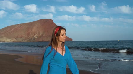 włosy : Woman in sunglasses and blue dress walking along a black volcanic beach Wideo