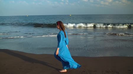 long hair : Woman in sunglasses and blue dress walking along a black volcanic beach Stock Footage
