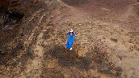 vítr : Aerial view of woman in a beautiful blue dress and hat stands on top of a mountain in a conservation area on the shores of the Atlantic Ocean. Tenerife, Canary Islands, Spain. Slow motion
