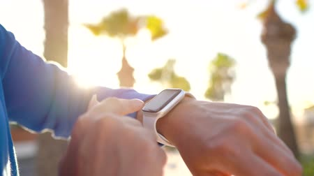 waga : Smartwatch. Woman using smart watch. Closeup of female touching touch screen on watch, entering watch app before run