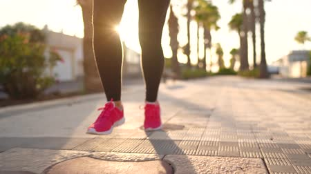 corps humain : Close up of legs of a woman running along the palm avenue at sunset Vidéos Libres De Droits