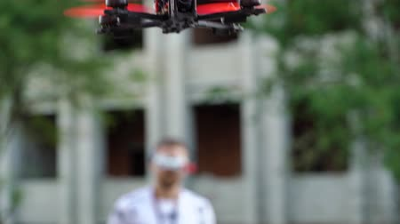 air vehicle : Male pilot manages FPV freestyle drone in flight
