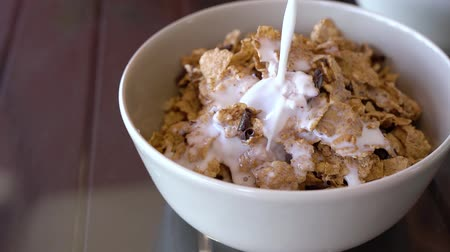 диеты : Tasty breakfast - milk is poured into a bowl with cornflakes and chocolate chips Стоковые видеозаписи