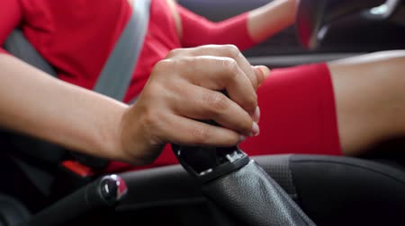 auto parking : Close-up of woman driver in a red dress fastens her seat belt, changes gear and starts moving Stock Footage