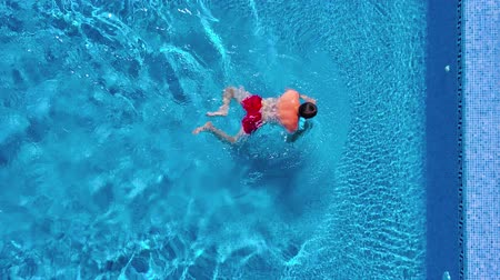 nurkowanie : Aerial view of man in red shorts swims in the pool and get out of it Wideo