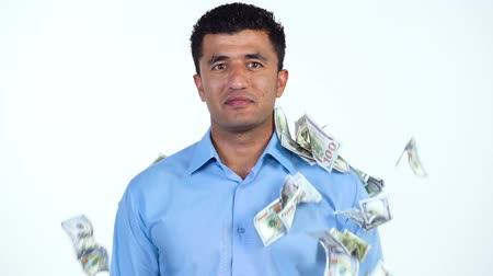 waluta : Slow motion of arab man standing on a white background, and a lot of dollar bills are suddenly thrown at him from different sides