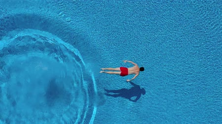 corps humain : View from the top as a man dives into the pool and swims under the water Vidéos Libres De Droits