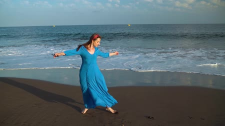 long hair : Woman in a beautiful blue dress and sunglasses enjoys a walk along the beach, joyfully spinning. Slow motion
