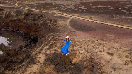 vítr : Aerial view of woman in a beautiful blue dress and hat stands on top of a mountain in a conservation area on the shores of the Atlantic Ocean. Tenerife, Canary Islands, Spain