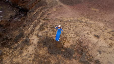 旅行の目的地 : Aerial view of woman in a beautiful blue dress and hat stands on top of a mountain in a conservation area on the shores of the Atlantic Ocean. Tenerife, Canary Islands, Spain