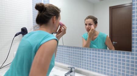 щеткой : Pretty woman applying base under makeup or foundation with sponge in front of bathroom mirror