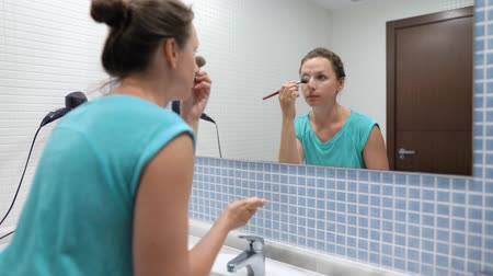 щеткой : Pretty woman powdering face with makeup brush in front of bathroom mirror Стоковые видеозаписи