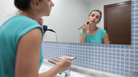 щеткой : Pretty woman doing face contouring in front of bathroom mirror